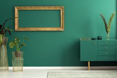 Plants in living room. Fresh plants placed in living room interior with green cupboard and gold mockup frame hanging on the wall royalty free stock image