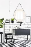 Plants and mirror in black and white bathroom interior with checkered floor and stool. Real photo. Concept royalty free stock images