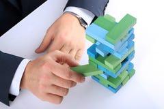 Planung, Risiko und Strategie im Geschäft, Geschäftsmann, der einen Holzklotz von einem Turm hinausgeht Lizenzfreie Stockfotografie