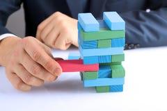 Planung, Risiko und Strategie im Geschäft, Geschäftsmann, der einen Holzklotz von einem Turm hinausgeht Lizenzfreie Stockfotos