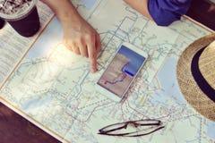 Planungsurlaubsreise der jungen Frau mit Karte Lizenzfreie Stockfotos
