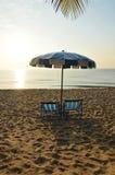 Plażowi brezentowi łóżka z błękitnym i białym parasolem Zdjęcia Royalty Free