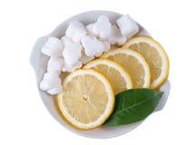 Plaque avec des cubes en sucre, des parts de citron et le vert Photographie stock