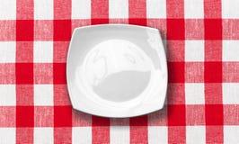 Plaque blanche sur la nappe contrôlée rouge de tissu Photographie stock libre de droits