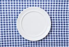 Plaque blanche sur le tissu checkered bleu et blanc Photo stock