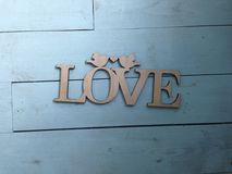 Plaque carved in wood with an inscription love on a blue background Stock Photo