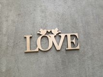 Plaque carved in wood with an inscription love on a gray background Royalty Free Stock Photo