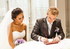 Plaque d'immatriculation de mariage de signature de jeune mariée ou contrat l'épousant Photos libres de droits
