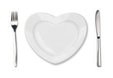 Plaque dans la forme du coeur, du couteau de table et de la fourchette Images stock