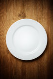 Plaque de dîner blanche sur le bois photographie stock libre de droits