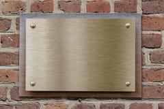 Plaque de métal de laiton ou de bronze sur le brickwall photo stock
