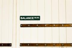 Plaque de rue de boulevard d'équilibre au-dessus des crochets de vêtements Images stock