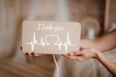 Plaque en bois avec l'inscription je t'aime dans des mains Image libre de droits