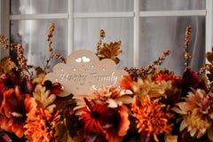 Plaque en bois mignonne avec la famille heureuse d'inscription parmi des fleurs Images stock