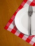 Plaque et fourchette blanches sur la nappe en bois de la table W Images libres de droits