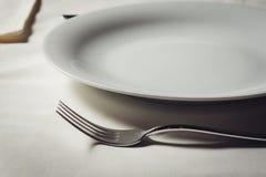 Plaque et fourchette blanches sur la vieille table en bois Photo stock
