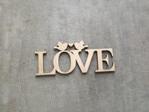 Plaque in hout met een inschrijvingsliefde wordt gesneden op een grijze achtergrond die Royalty-vrije Stock Foto