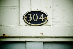 304 on plaque. 304 on oval plaque of wooden hut royalty free stock photos