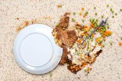 Plaque renversée de nourriture sur le tapis Photos stock