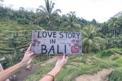 Plaque signalétique en bois avec l'histoire d'amour des textes dans Bali dans les mains de femme sur un fond tropical de terrasse Photographie stock libre de droits