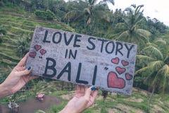 Plaque signalétique en bois avec l'histoire d'amour des textes dans Bali dans les mains de femme sur un fond tropical de terrasse Photos stock