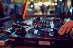 Plaque tournante, main du DJ sur le disque vinyle à la boîte de nuit fond blured photographie stock