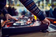 Plaque tournante, main du DJ sur le disque vinyle à la boîte de nuit fond blured photo stock