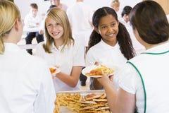 Plaques de portion de Lunchladies du déjeuner dans une école Photos libres de droits