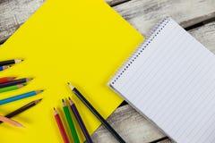 Plaquette, crayons de couleur et bloc-notes jaunes Images stock