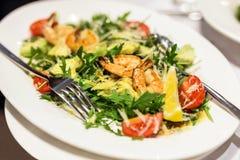 Plaquez avec le salat mélangé de crevettes Plat avec les crevettes roses, l'arugula, la tomate et le fromage Repas sain délicieux photos libres de droits