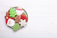 Plaquez complètement des biscuits savoureux de Noël sur la table en bois Photos stock