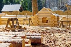 Plaschadka de la construcción que procesa y casas de las cabañas de madera de la asamblea hechas de la madera redonda Fotografía de archivo libre de regalías