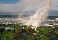 Plaska wave på stendike med regnbågen Royaltyfria Foton