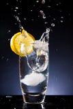 Plaskande exponeringsglas av kallt vatten på en svart bakgrund Arkivbilder