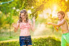 Plaskande flicka för pojke med vattenvapnet, solig sommarträdgård Royaltyfri Bild