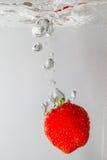 Plaskande jordgubbe in i ett vatten Royaltyfri Fotografi