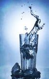Plaskande vatten av is i ett kallt exponeringsglas av vatten Fotografering för Bildbyråer