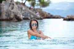 plaskande vatten för bikinimodell Royaltyfri Foto