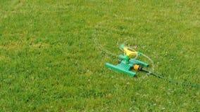 Plaskande vatten för gräsmattaspridare över grönt gräs lager videofilmer