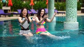 Plaskande vatten för två kvinnavänner i simbassäng arkivfilmer