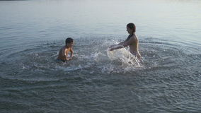 Plaskande vatten för två ungar i floden på solnedgången stock video