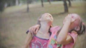 Plaskande vatten för vänner på två upphetsade unga små flickor som täckas i färgpulver stock video