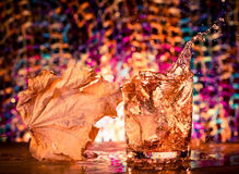 Plaskande whiskyexponeringsglas Arkivfoto