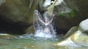 Plaskar den härliga flickan för ultrarapid på vatten vid händer i bergfloden i grön tropisk skog med den lilla vattenfallet lager videofilmer