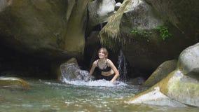 Plaskar den härliga flickan för ultrarapid på vatten vid händer i bergfloden i grön tropisk skog med vattenfallet stock video