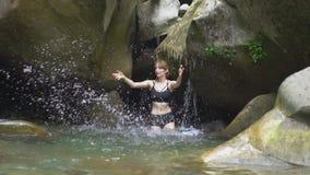 Plaskar den härliga flickan för ultrarapid på vatten vid händer i bergsjön i grön tropisk skog med den lilla vattenfallet arkivfilmer