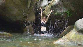 Plaskar den härliga flickan för ultrarapid på vatten vid händer i bergsjön i grön tropisk skog med den lilla vattenfallet och stock video