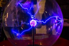 Plasma ball with smooth magenta-blue flames on a dark background. Plasma ball with smooth magenta - blue flames stock photo