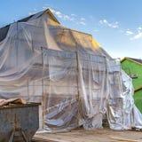 Plast- ark f?r fyrkant som t?cker ett oavslutat hus och scaffoldings mot bl? himmel arkivbilder