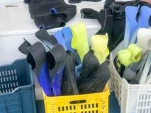 Plast- ask, korg med mång--färgade rubber dykningfena för att simma ombord en ask, fartyg, kryssningeyeliner Arkivfoto